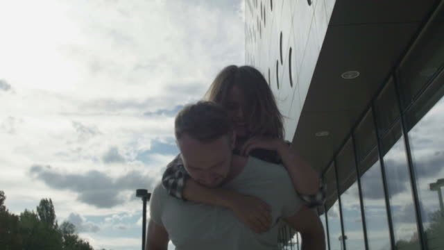 Young handsome man giving his blonde girlfriend a piggy back in the city. video