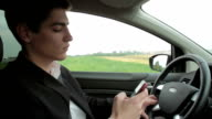 Young handsome man using mobile phone in the car video
