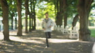 Young Handsome Man Using Mobile Phone While Running Outdoors. video