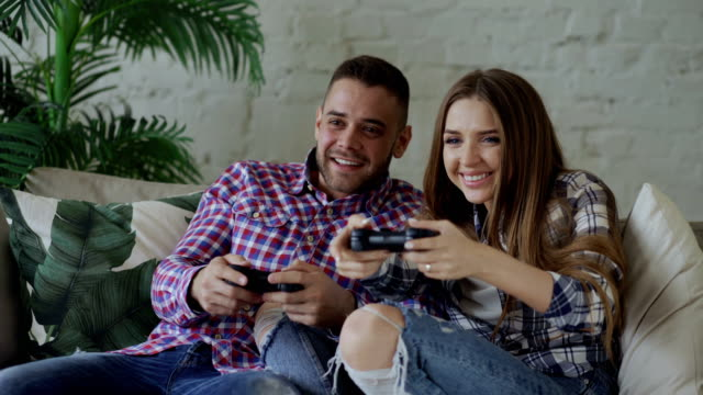 Young happy and loving couple play console game with gamepad and have fun sitting on couch in living room at home video