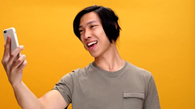Young happy asian man talking by phone waving and showing thumbs up isolated over yellow background. video