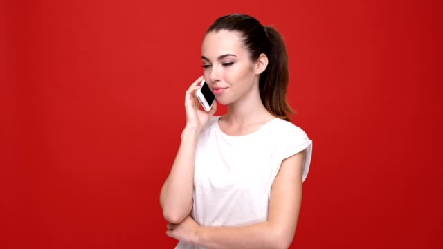 Young happy caucasian lady talking by mobile phone and wink to camera over red background. video