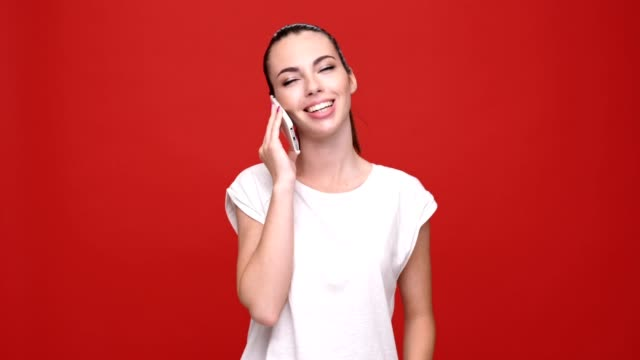 Young happy caucasian lady talking by mobile phone over red background. video