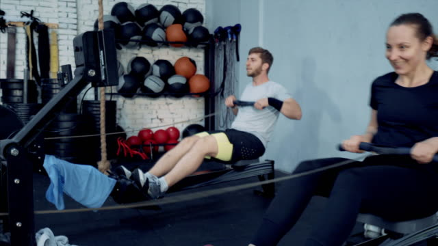 Young happy couple doing exercises on rowing machine. video