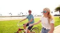 Young Happy Couple Riding Bikes At Beach, Summer Lifestyle HD video