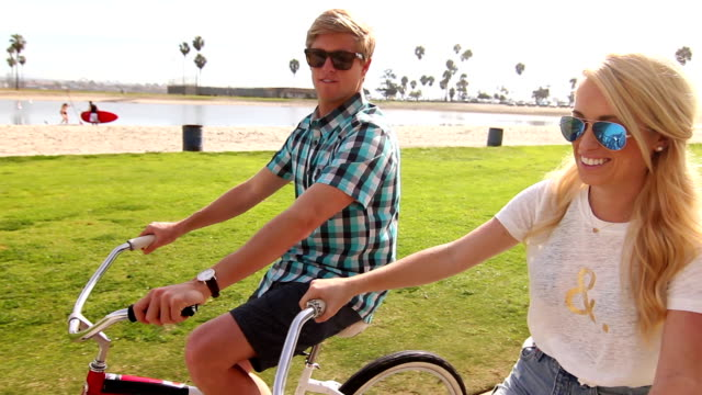 Young Happy Couple Riding Bikes At Beach video