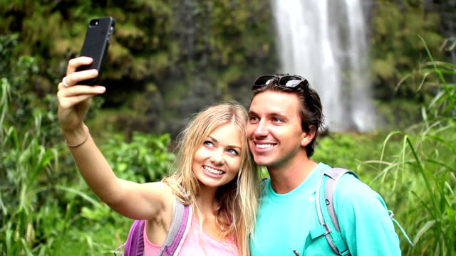 Young Happy Couple Taking Selfie Outside By Waterfall video