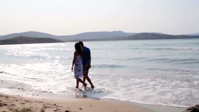 Young happy couple walking beach holding hands video