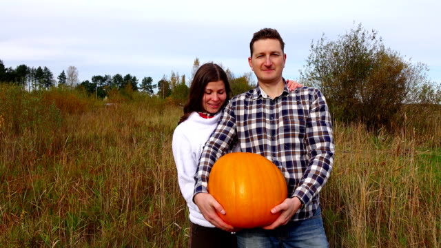 Young happy family stay in field with big harvested pumpkin, thumbs up video