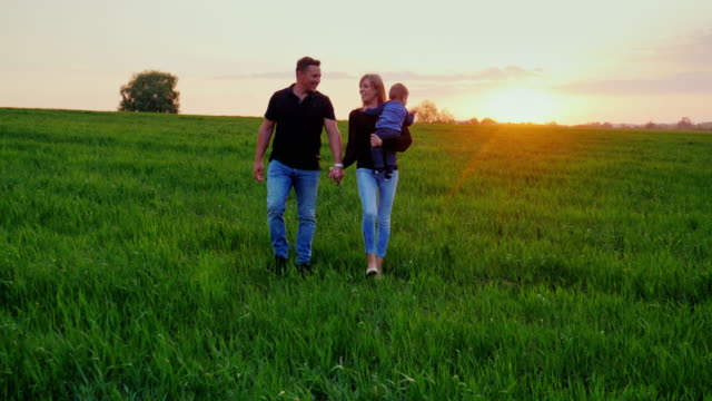 Young happy family with baby. They go to the picturesque green field at sunset. Steadicam shot video