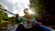 Young happy male paddling kayak, extreme sports video