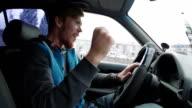 Young happy man driving a car dancing. Inside shot video