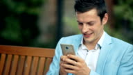 Young happy man sitting in the park and using smartphone video