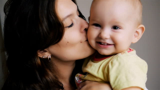 Young Happy Mother Holding her Newborn Child. Family at home. Beautiful smiling Mom and Happy Baby Together video