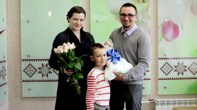 Young happy parents holding a newborn baby, standing on the threshold of the hospital. video