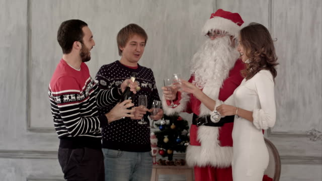 Young happy smiling friends with santa open and drink champagne. Christmas and Happy New Year video