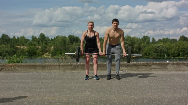Young happy sports couple working out with barbell together video