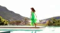 Young happy woman dancing poolside video