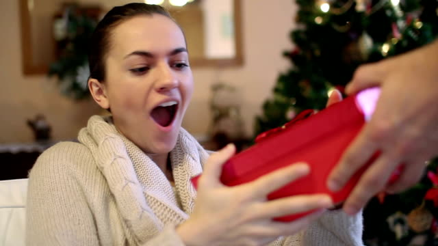 Young happy woman gets present, christmas tree in background video