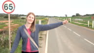 Young happy woman walking by a countryside road hitchhiking. Looking for a ride to start a journey video