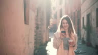 Young happy woman walking in city centre at morning, using smartphone. Girl surfing the Internet, texting with someone video