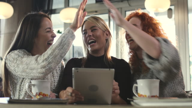 Young happy women gossiping and laughing while using touchpad in a cafe. video