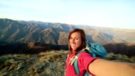 Young hiker taking selfie at mountain top video