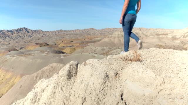 Young hiker woman trekking Badlands National park reaching the rocky mountaintop video