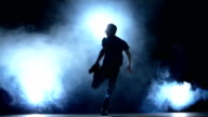 Young hiphop dancer starts making a move, smoke, silhouette, slow motion video