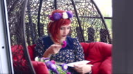 Young hippie bohemian style woman resting and enjoying a book reading in swing chair on a balcony video
