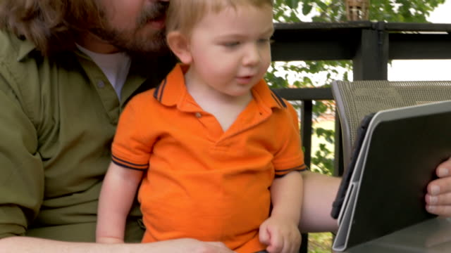 A young hipster father holds a tablet for his son as they watch a video video