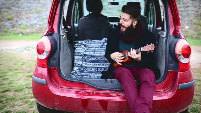 Young hipster having fun on road trip video