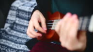 Young hipster playing ukulele video