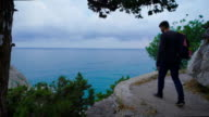 Young hipster with backpack suitable to the edge and looks at the stunning views video