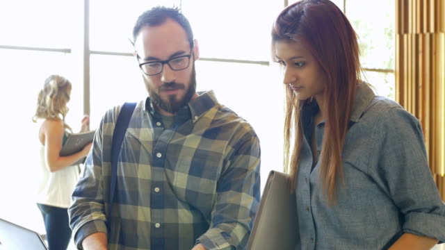 Young Hispanic businesspeople meeting in modern casual office setting video