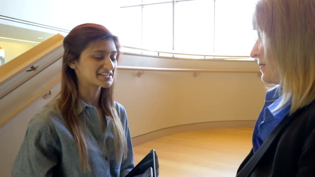Young Hispanic businesswoman talking with office coworker in lobby video