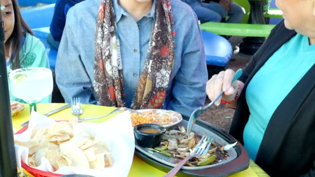 Young Hispanic woman having meal with grandmother outdoors on restaurant patio video