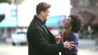 Young interracial couple walking together in city video