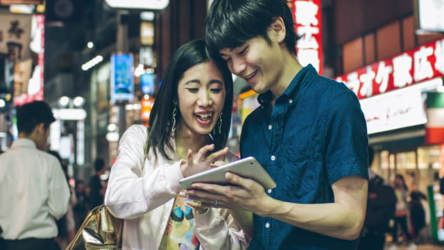 Young Japanese couple having fun using digital tablet video