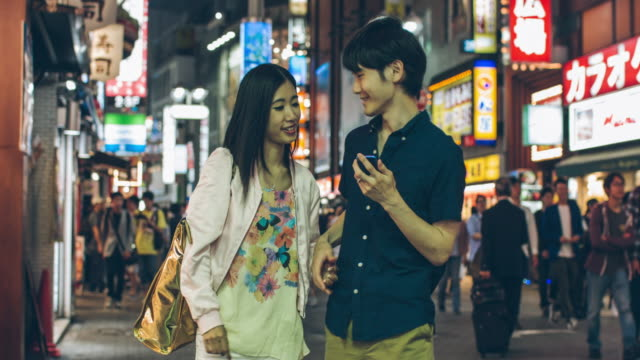 Young Japanese couple looking for an address at mobile phone video