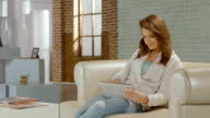 Young lady enjoying work in new tablet PC app, smiling video