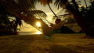 Young lady lying in hammock, enjoying tropical vacation in paradise at beautiful golden sunset video
