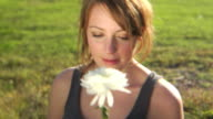 HD CRANE: Young lady smells a flower video
