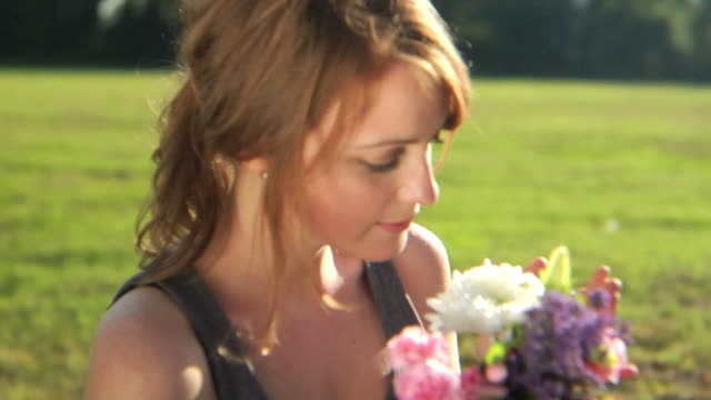 HD CRANE: A young lady smells flowers video