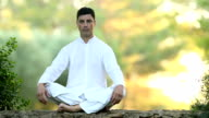 Young latin man sitting on the wall and meditating video