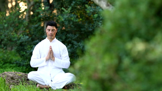 young latin men in white clothing doing meditation in the park video