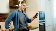 Young laughing man watching streaming movie on digital tablet eating cereals with headphones video