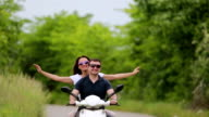 Young love couple enjoying ridding on scooter video