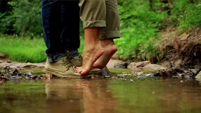 A young loving couple hugging and kissing. Two lovers, man and woman barefoot near the water. video