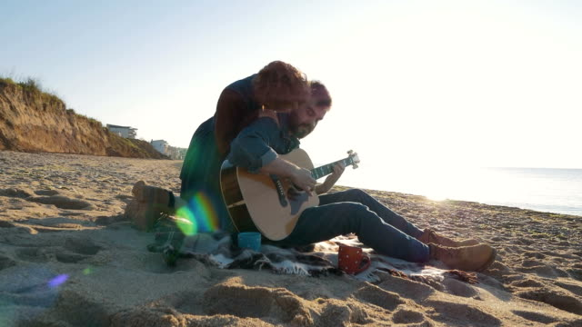 Young loving couple playing guitar on the beach, steadycome shot video